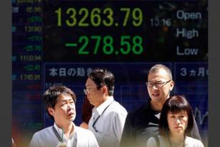 Pejalan kaki menunggu untuk menyeberang di depan Nikkei 225 indeks saham harian di Tokyo, Jepang, 28 Agustus, 2013. Kemungkinan meningkatnya aksi militer Barat terhadap Suriah memukul pasar saham Asia dan membuat harga minyak melonjak.
