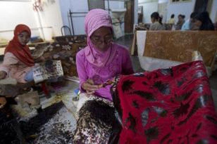 Para perajin membatik di bengkel kerja di kawasan Trusmi, Cirebon, Jawa Barat, Minggu (28/7/2013). Batik merupakan oleh-oleh yang biasa dibeli oleh para pemudik yang melewati jalur Cirebon.