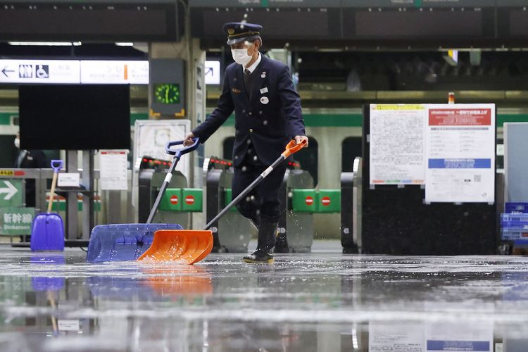 Seorang pekerja menyapu air yang menggenangi lantai stasiun kereta api Fukushima, Jepang, usai gempa bumi 7,3 magnitudo pada Sabtu (13/2/2021) tengah malam. Gempa ini mengguncang prefektur Fukushima, Miyagi, dan area lainnya di timur Jepang, tetapi tidak ada risiko tsunami.