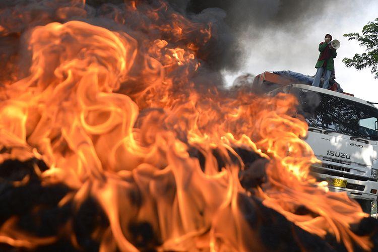 Sejumlah mahasiswa Universitas Islam Negeri (UIN) Makassar membakar ban bekas saat berunjuk rasa, di depan kampus UIN Alauddin, Makassar, Sulawesi Selatan, Selasa (6/10/2020). Dalam aksi unjuk rasa tersebut mereka menolak Undang-undang (UU) Omnibus Law Cipta Kerja yang telah disahkan oleh DPR pada Senin (5/10/2020) karena dinilai merugikan para pekerja dan hanya menguntungkan bagi pengusaha.