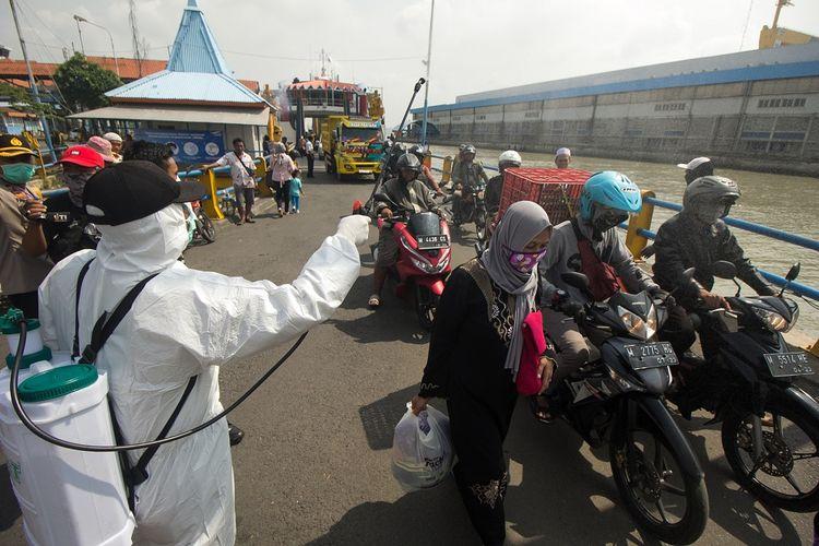 Petugas menyemprotkan larutan disinfektan kepada penumpang yang turun dari kapal KMP Gajah Mada di Penyeberangan Ujung-Kamal, Surabaya, Jawa Timur, Sabtu (28/3/2020). Kegiatan itu untuk mencegah penyebaran Virus Corona (COVID-19). ANTARA FOTO/Didik Suhartono/ama.