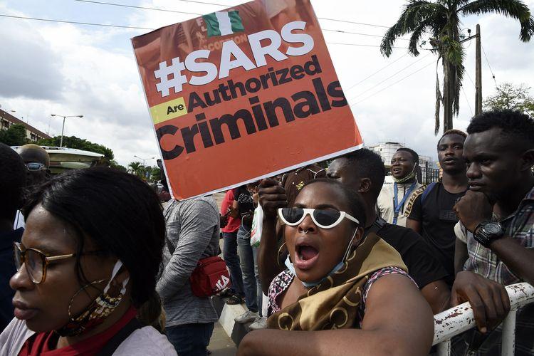 Demonstran membawa papan bertuliskan SARS (Pasukan Khusus Anti-Perampokan) adalah penjahat yang sebenarnya, dalam aksi unjuk rasa menuntut pembubaran unit polisi yang kontroversial itu di Ikeja, Nigeria, Kamis (8/10/2020).