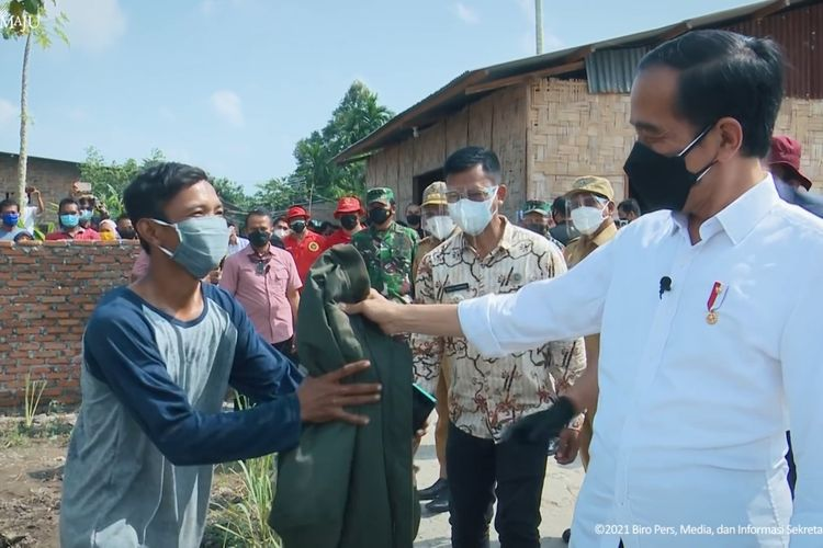 Foto tangkapan layar YouTube Sekretariat Presiden: Presiden Joko Widodo memberikan jaket kepunyaannya ke warga di Deli Serdang, Sumatera Utara, Kamis (16/9/2021).