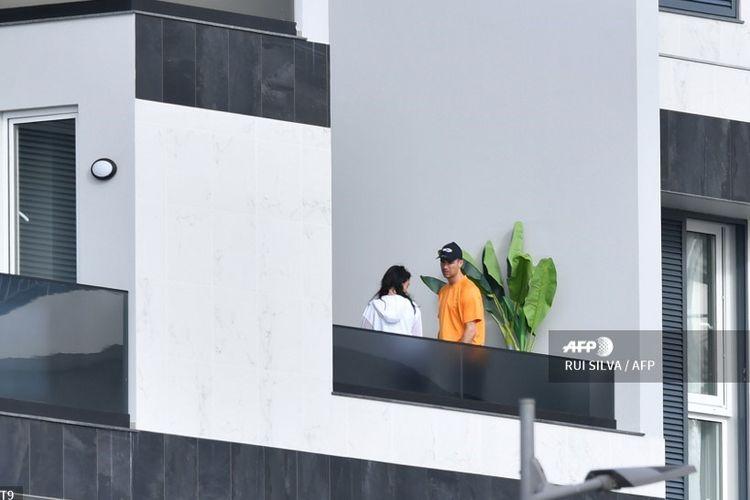 Penyerang Juventus, Cristiano Ronaldo, dan pacarnya, Georgina Rodriguez, berdiri di balkon rumah mereka di Funchal pada 13 Maret 2020. Cristiano Ronaldo menjalani karantina mandiri di Madeira sejak rekan setimnya, Daniele Rugani, positif terjangkit virus corona.