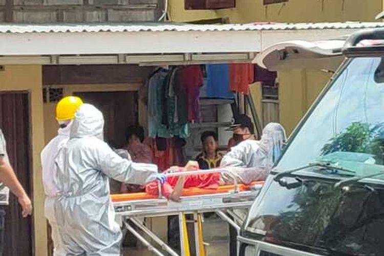 Petugas kesehatan dengan menggunakan pakaian alat pelindung diri lengkap terlihat berusaha mengevakuasi warga yang ditemukan pingsan mendadak di sisi jalan lintas timur Palembang-Ogan Ilir Desa Tebing Gerinitng senin siang.