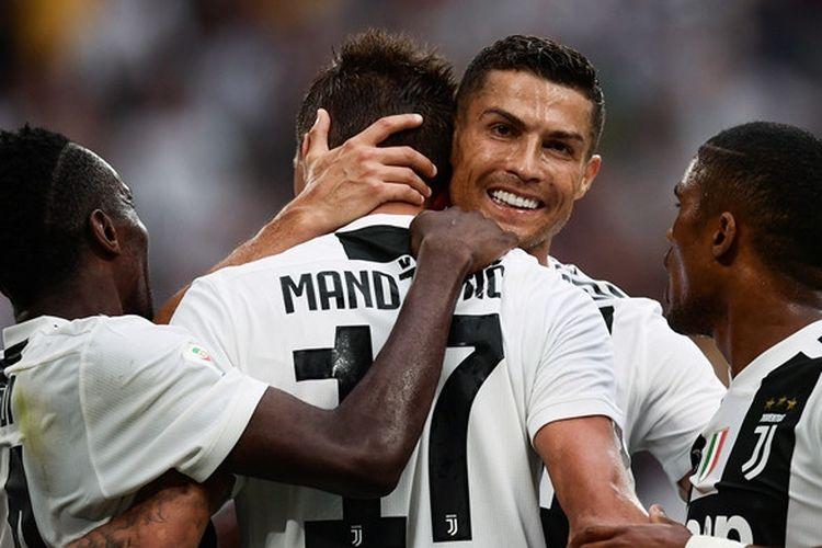 Megabintang Juventus, Cristiano Ronaldo (kedua dari kanan), memeluk Mario Mandzukic yang mencetak gol ke gawang Lazio dalam laga Liga Italia di Allianz Stadium, Turin pada 25 Agustus 2018.