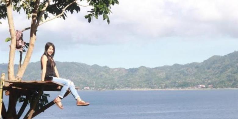 Berfoto di Rumah Pohon Urongo dengan latar belakang pesona Danau Tondano di Sulawesi Utara.