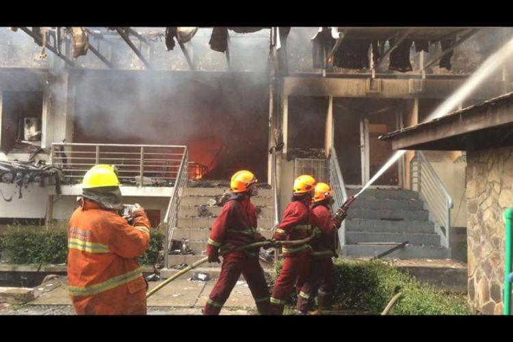 Petugas pemadam kebakaran saat memadamkan api di gedung Pascasarjana Studi Pembangunan di kampus Institut Teknologi Bandung (ITB), Minggu (30/12/2018) malam.