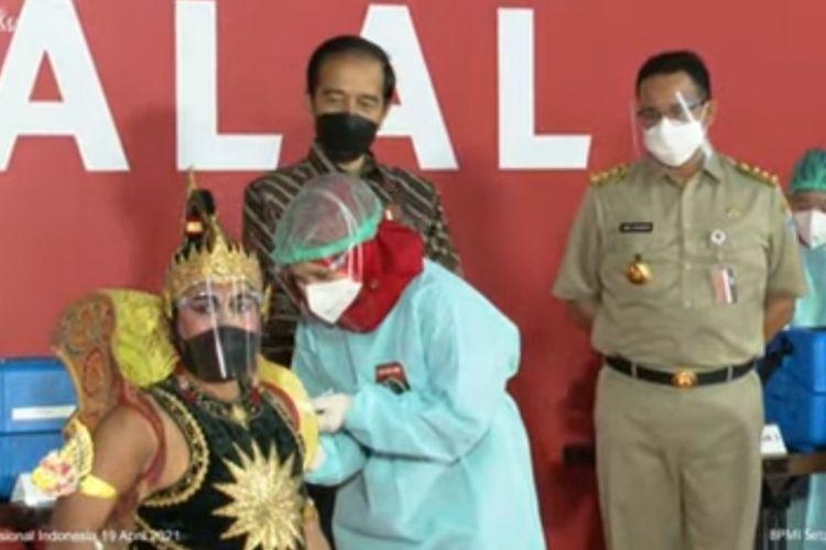 Presiden Joko Widodo bersama Gubernur DKI Jakarta menyaksikan vaksinasi Covid-19 kepada seniman wayang orang di Galeri Seni Indonesia, Senin (19/4/2021). Kegiatan vaksinasi massal pada Senin menyasar para seniman dan budayawan.