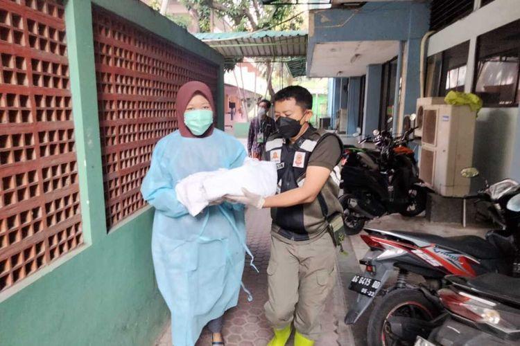 Tim dokter dan petugas Satpol PP memindah bayi yang dilahirkan PMI secara prematur di komplek Asrama Haji Surabaya, Kamis (22/7/2021).