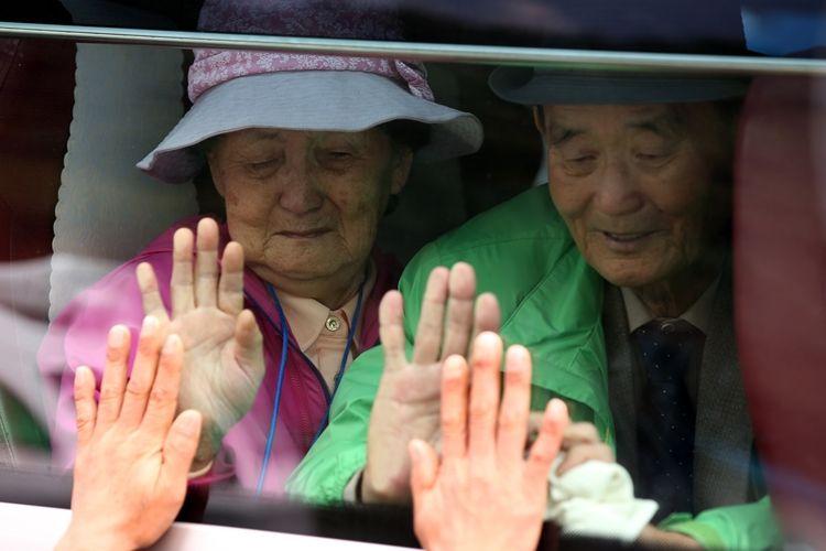 Warga Korea Selatan memberikan salam perpisahan dari dalam bus kepada keluarga mereka yang merupakan warga Korea Utara usai reuni yang dilakukan di kawasan pegunungan Kumgang, 26 Oktober 2015.