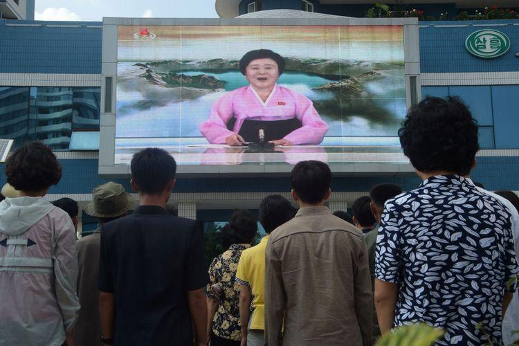 Warga menyaksikan video pada layar besar di Jalan Mirae Scientists di Pyongyang, Korea Utara, yang menampilkan pembawa acara Ri Chun-Hee mengumumkan berita bahwa negara tersebut berhasil menguji coba bom hidrogen pada Minggu (3/9/2017).