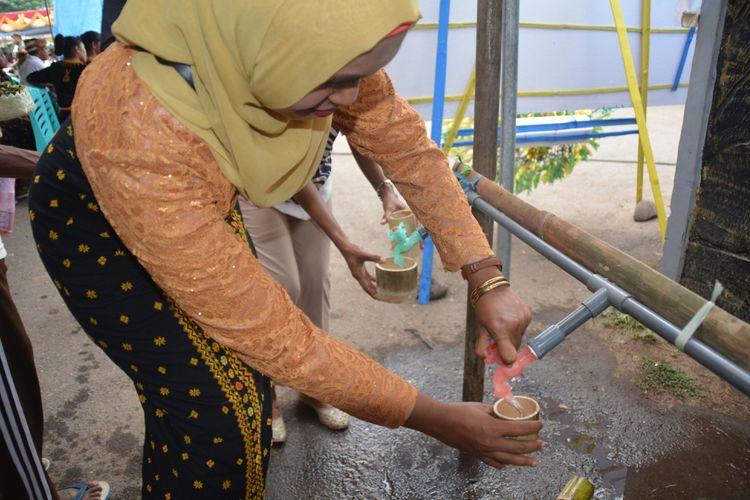 Seorang warga Nagekeo sedang menadah air minum bersih dengan gelas bambu untuk dihidangkan kepada tamu yang sedang mengikuti syukuran pemimpin baru Kabupaten Nagekeo, Flores, NTT, Kamis (27/12/2018).
