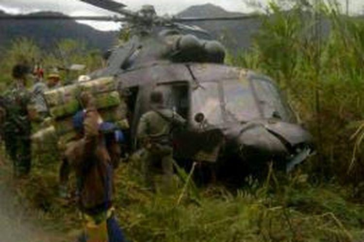 Helikopter TNI AD jenis MI-17 yang melakukan pendaratan darurat di Kampung Abnu Sibil, Distrik Okbibab, Kabupaten Pegunungan Bintang. Terlihat sejumlah bagian pesawat mengalami kerusakan, sementara personil TNI dari Koramil Okbibab dan Satgas 126 mengangkut logistik serta berjaga di lokasi kejadian.