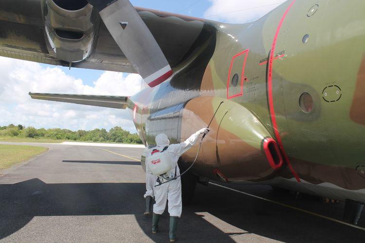 Sejumlah petugas tengah menyemprot disinfektan terhadap pesawat TNI C-130 Hercules yang membawa alat kesehatan dari Shanghai, China.