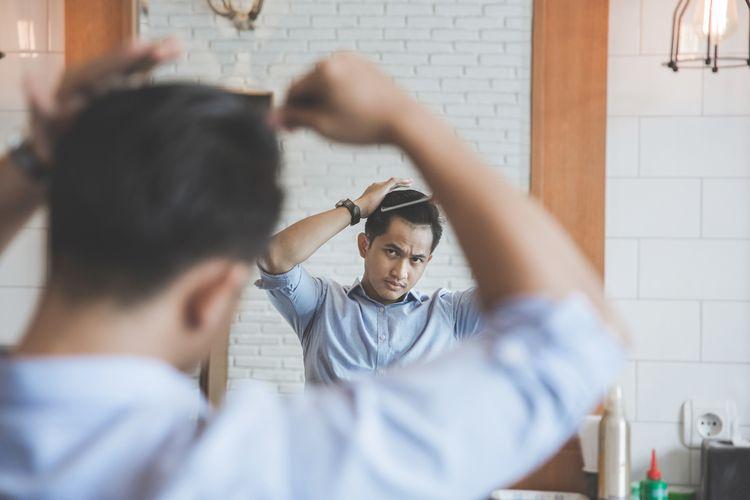Ilustrasi pria sedang menata rambut dengan pomade.