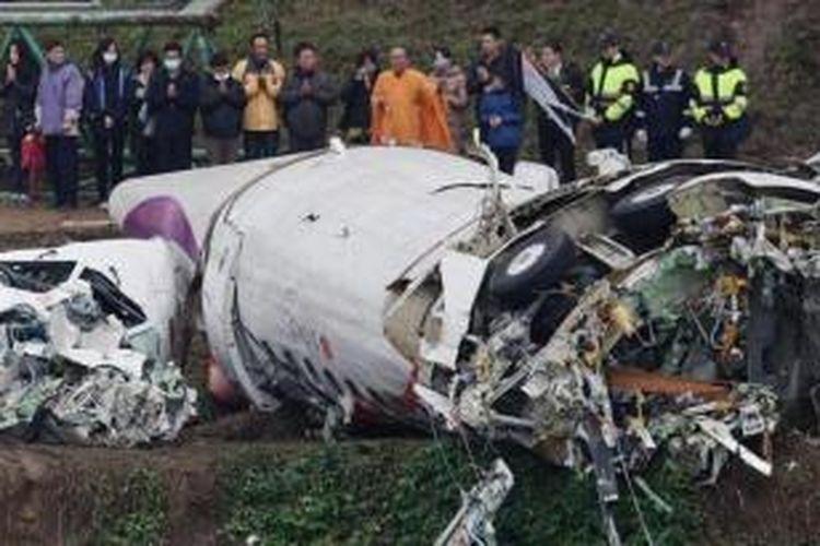 Sekelompok anggota keluarga korban jatuhnya pesawat TransAsia Airways menggelar doa bersama di dekat reruntuhan pesawat yang sudah dipindahkan, Jumat (6/2/2015).