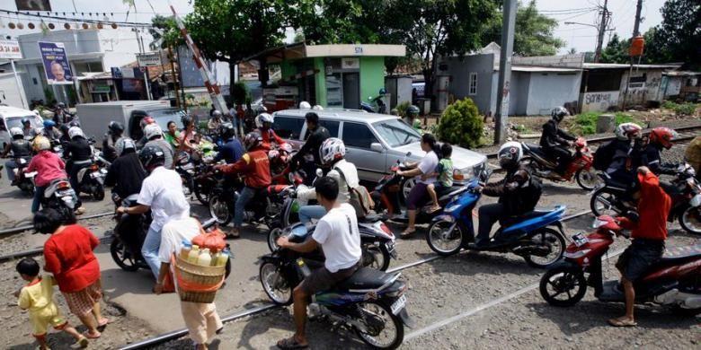 Pengguna jalan melintas di perlintasan kereta api di sekitar Pasar Bintaro, Pesanggrahan, Jakarta Selatan, Kamis (4/4/2013). Pertemuan lalu lintas dari empat arah di  pintu perlintasan itu menjadi penyebab kemacetan. Kondisi ini tentunya menyebabkan kawasan itu rawan kecelakaan yang melibatkan kereta api.