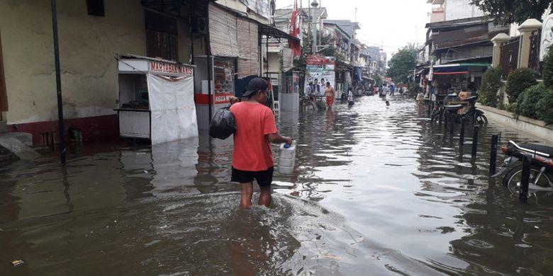 Seorang warga melintas di Jalan Kerapu 3 Muara Angke yang terendam banjir, Jumat (25/1/2019).