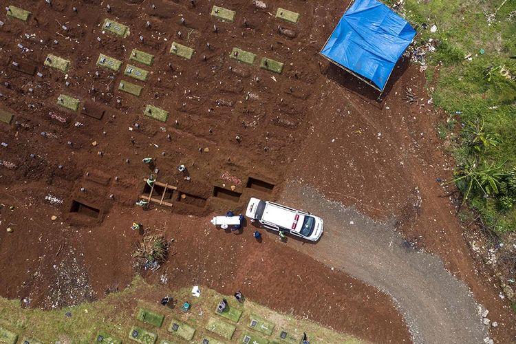 Foto dirilis Sabtu (19/9/2020), memperlihatkan petugas penggali makam jenazah Covid-19 bersiap menurunkan peti di kompleks pemakaman Pondok Ranggon. Selain tenaga medis yang menjadi garda terdepan penanganan virus corona, salah satu pahlawan lain juga patut diberikan apresiasi tinggi adalah petugas pemakaman jenazah Covid-19.