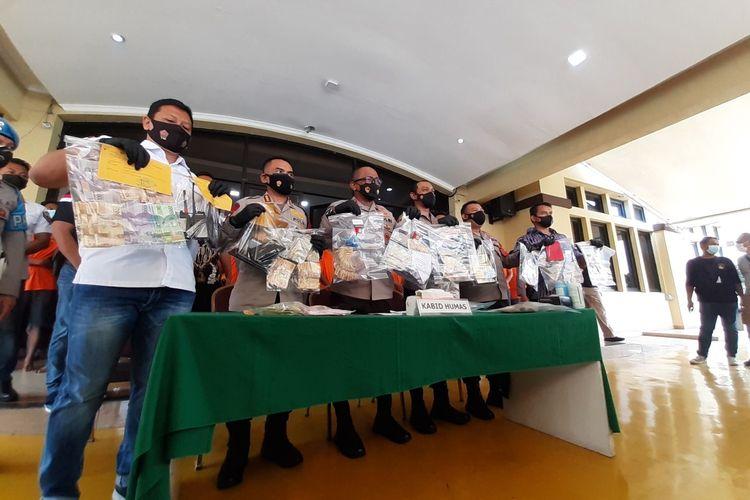 Kepala Bidang Hubungan Masyarakat Polda Metro Jaya, Komisaris Besar Polisi Yusri Yunus, memegang barang bukti penangkapan tersangka pungutan liar (pungli) di Polrestabes Jakarta Utara, Jumat (11/6/2021).