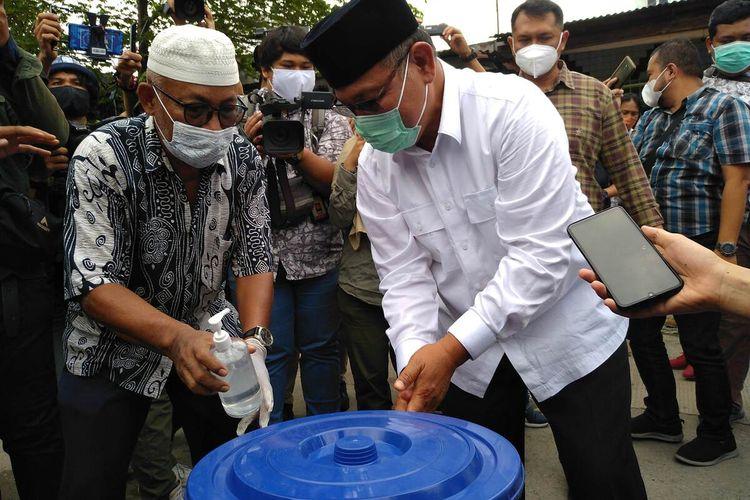 Calon Wali Kota Medan, Akhyar Nasution mencuci tangan sebelum mencoblos di TPS 22 di Kelurahan Brayan Darat II, Kecamatan Medan Timur. Akhyar yang tiba bersama keluarganya optimis memenangi pilkada ini.