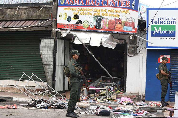 Aparat keamanan berjaga di dekat bangunan toko yang rusak akibat serangan yang dilakukan sebuah kelompok massa di Minuwangoda, Sri Lanka, Selasa (14/5/2019). Satu orang dilaporkan tewas dalam aksi kerusuhan anti-Muslim di Sri Lanka pada Senin, 13 Mei lalu, hingga diberlakukannya jam malam secara nasional.