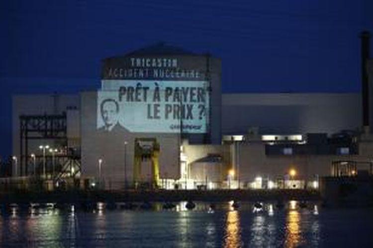 Sebuah gambar Presiden Perancis Francois Hollande disorotkan para aktivis Greenpeace sesaat sebelum menerobos masuk ke dalam reaktor nuklir Tricastin, di Perancis Selatan.