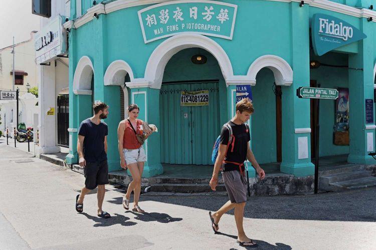 Wisatawan berjalan menyusuri sudut Kota Penang pada hari pertama lockdown di Malaysia, Rabu (18/3/2020). Pemerintah Malaysia mengumumkan keputusan melakukan lockdown selama dua pekan untuk memerangi virus corona.