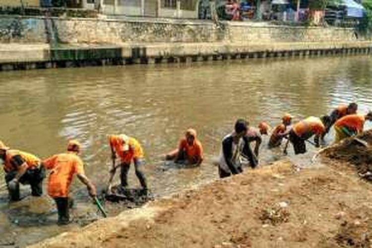 Petugas PPSU dan PHB Sudin Kebersihan bahu-membahu membersihkan lumpur di Kali Ciliwung belakang Kantor Kelurahan Kwitang, Senen, Jakarta Pusat, Selasa (17/5/2016).