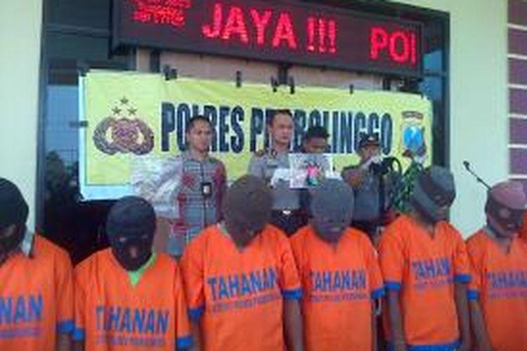 Kapolres AKBP Iwan Setiawan menunjukkan foto korban pembunuhan, di belakang para tersangka.