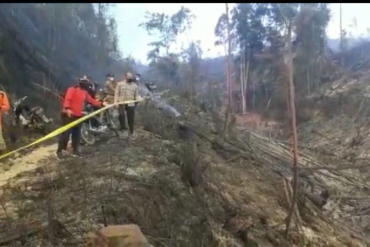 Petugas kepolisian bersama TNI memasang garis polisi pada lokasi kebakaran hutan lindung Bukit Suligi di Desa Kumain, Kecamatan Tandun, Kabupaten Rokan Hulu, Riau, Kamis (22/7/2021).