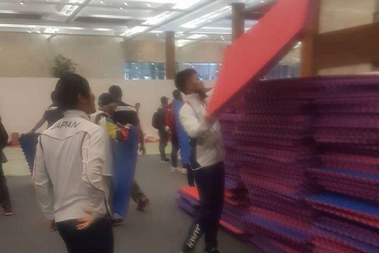 Tim Karate Jepang ikut membantu panitia Asian Games 2018 membersihkan matras latihan di Venue Karate Jakarta Convention Center, Senayan, Jakarta, Senin (27/8/2018)