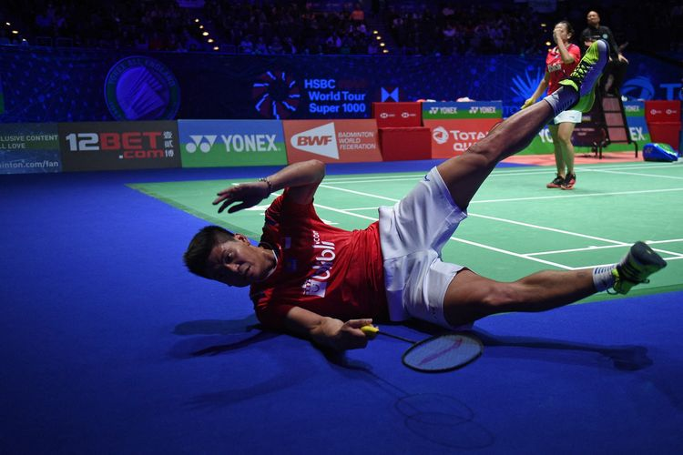 Indonesia's Praveen Jordan (L) playing with Indonesia's Melati Daeva Oktavianti stumbles as they play against Thailand's Dechapol Puavaranukroh and Sapsiree Taerattanachai  during their All England Open Badminton Championships mixed doubles final match in Birmingham, central England, on March 15, 2020. (Photo by Oli SCARFF / AFP)