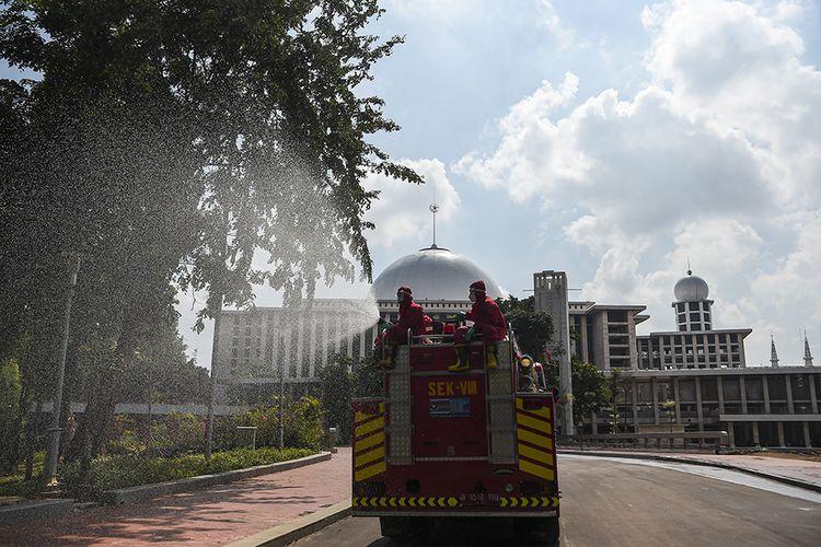 Petugas pemadam kebakaran dan penyelamatan DKI Jakarta menyemprotkan disinfektan di halaman Masjid Istiqlal Jakarta, Rabu (3/6/2020). Penyemprotan tersebut sebagai upaya mencegah penyebaran virus corona (COVID-19) di rumah ibadah jika nantinya kembali dibuka untuk umum saat pemberlakuan tatanan hidup normal baru (new normal).
