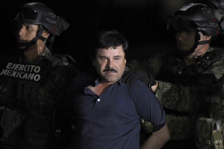 Dalam foto yang diambil pada 8 Januari 2016 ini terlihat gembong narkoba Joaquin El Chapo Guzman digiring menuju sebuah helikopter di sebuah bandara di Mexico City setelah militer menangkapnya di Los Mochis, negara bagian Sinaloa setelah sempat kabur dari penjara.