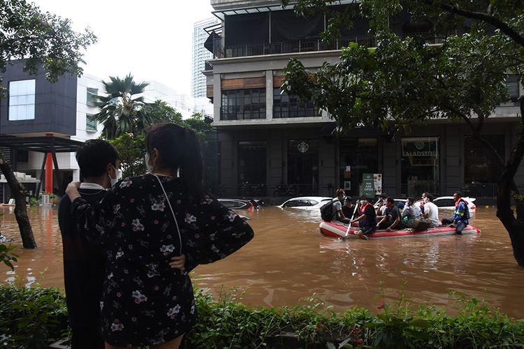 Petugas mengevakuasi warga menggunakan perahu karet saat banjir melanda kawasan Kemang, Jakarta Selatan, Sabtu (20/2/2021). Banjir yang terjadi akibat curah hujan tinggi serta drainase yang buruk membuat kawasan Kemang banjir setinggi 1,5 meter.