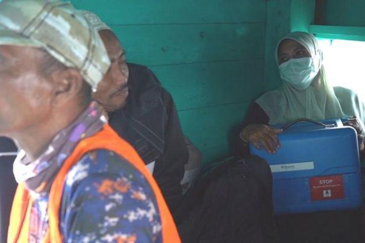Arina Astuti, Koordinator Imunisasi Puskesmas Pulo Aceh, membawa kotak berisi vaksin Covid-19 dengan menumpang kapal.