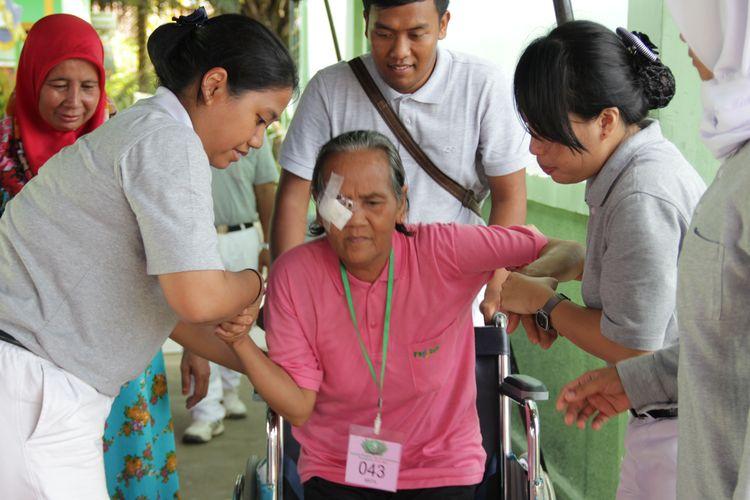 Para relawan Tzu Chi Sinar Mas membantu seorang pasien operasi katarak