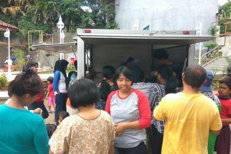 Warga sedang membeli nasi bungkus lauk apa saja dengan harga Rp 2.000 per bungkus di halaman parkir Masjid Al Ridwan Jatipadang, Pasar Minggu, Jakarta Selatan, Kamis (8/2/2018).