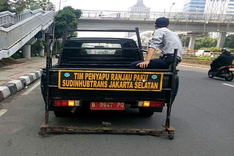 Mobil Suku Dinas Perhubungan Kota Administrasi Jakarta Selatan menyisir ranjau paku di Jalan MT Haryono dari arah Semanggi menuju Cawang, Senin (10/8).