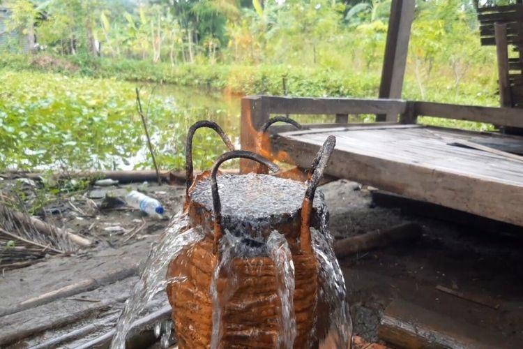 Sumber air keluar dari bekas sumur bor terbakar saat disulut api di Dukuh RT 006, RW 001, Krendowahono, Gondangrejo, Karanganyar, Jawa Tengah, Sabtu (20/3/2021).