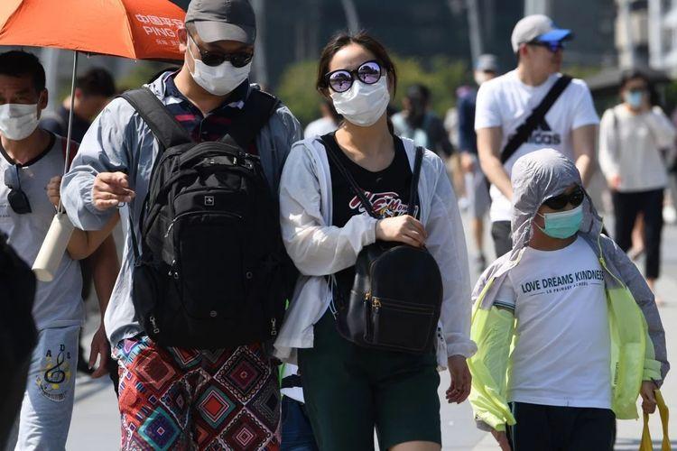 Pelancong mengenakan masker saat berada di Marina Bay Singapura