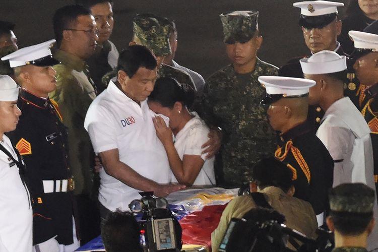 Presiden Rodrigo Duterte menghibur istri seorang personel marinir yang gugur dalam pertempuran di Marawi menghadapi militan Maute. Sejauh ini sudah 58 tentara Filipina tewas dalam baku tembak di Marawi.