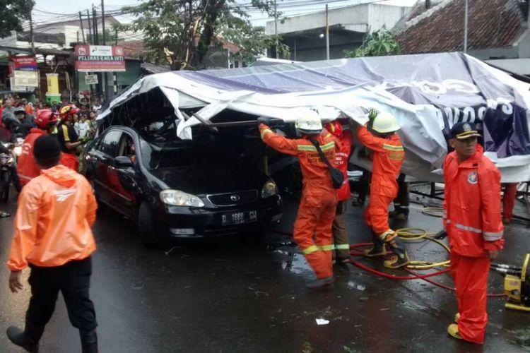 Sebuah mobil berisi satu keluarga tertimpa papan reklame akibat hujan deras disertai angin kencang di Kota Bandung, Rabu (19/4/2017).