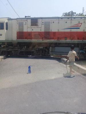 Sebuah postingan yang memperlihatkan anak-anak tengah menutup palang perlintasan kereta api dengan tali rafiah.