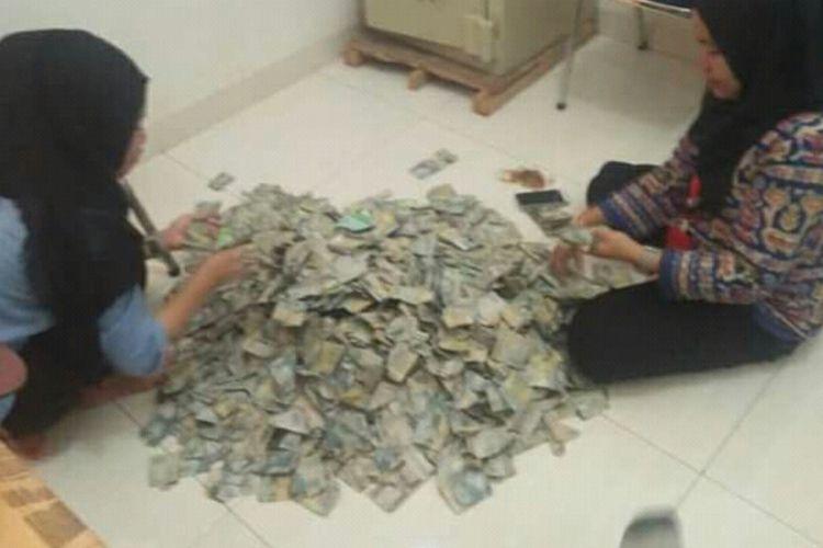Dua karyawan salah satu dealer penjualan sepeda motor di Kabupaten Bone, Sulawesi Selatan tengah menghitung sekarung uang dalam pecahan dua ribu rupiah yang dibawah oleh salah seorang warga untuk membeli motor. Kamis, (27/12/2018).