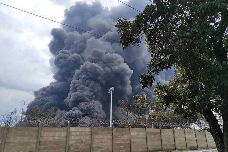 Asap hitam mengepul dari kebakaran tangki minyak T-130G milik PT Pertamina (Persero) RU VI Balongan Indramayu, Selasa (30/3/2021). Sebelum terbakar kilang ini meledak pada Senin (29/3/2021) kemarin malam diduga karena tersambar petir.
