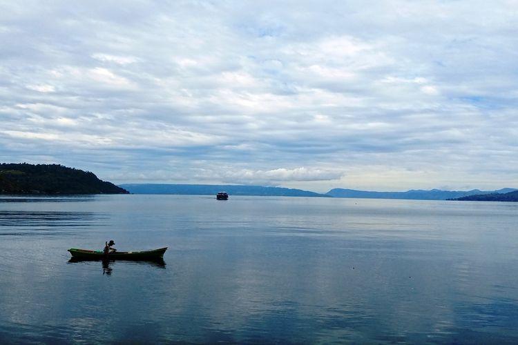 Danau Toba dengan Pulau Samosir dan nelayan pencari ikan, diambil dari salah satu sudut di Balige, Kabupaten Toba, Sumatera Utara