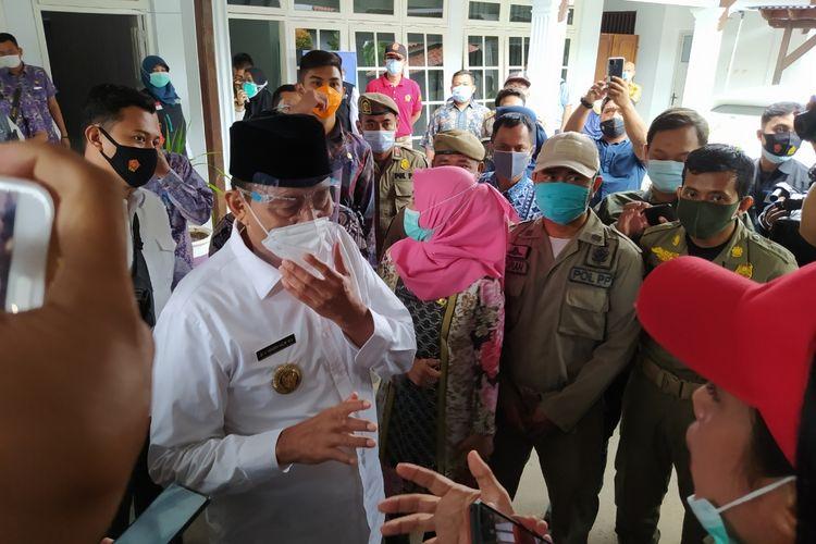 Gubernur Banten Wahidin tampak melakukan perdebatan dengan salah seorang awak media yang mempertanyakan keaslian vaksin dan meminta untuk memasuki ruang vaksinasi di Pendopo Kabupaten Tangerang, Kota Tangerang, Banten, Kamis (14/1/2021) sekitar pukul 09.30 WIB.